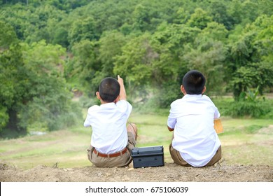Little poor Asian students in school uniforms sitting together looking at the  Mountain and pointing at something, little students in traditional school dress at countryside,thailand