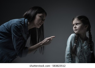Little poor girl looking at her mother