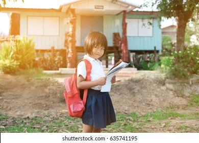 A little poor girl in school uniforms carry broken bag reading a book at school