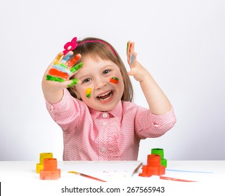 Little positive girl with painted hands in bright colors. On a white background