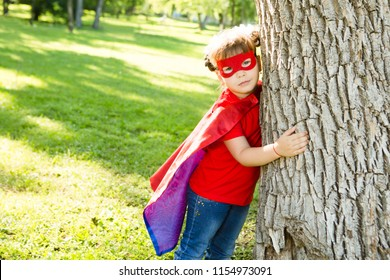 little power super hero child girl in a red raincoat playing outdoor. Superhero concept.
