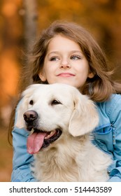 Little preaty girl with her golden retriever in autumn forest. Weekend