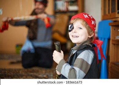 Little preschool boy of 4 years celebrating birthday in pirate costume, indoors with father on background