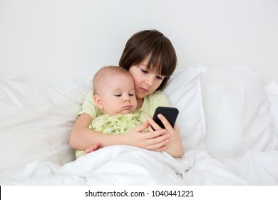 Little preschool boy laying in bed with his baby brother, playing on smart phone