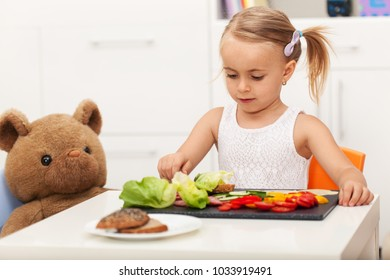 Little preschool girl having a healthy snack with her toy bear - playing at home