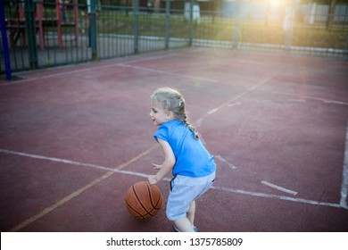 Little preschool girl playing basketball on court in the evening