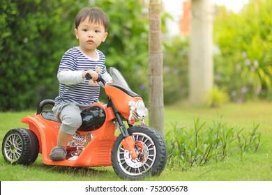 Little preschool kid boy driving orange motorbike toy at home.