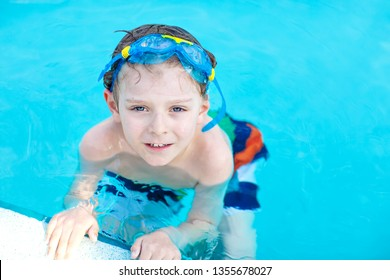 little preschool kid boy making swim competition sport. Kid with swimming goggles reaching edge of the pool . Child having fun in an swimming pool. Active happy child winning. sports, active leisure.