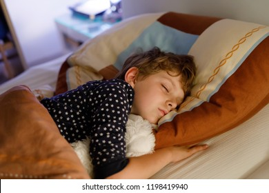 Little preschool kid boy sleeping in bed with colorful lamp.