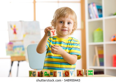 Little preschooler child boy playing with toy cubes and memorizing letters. Early education and preschool concept