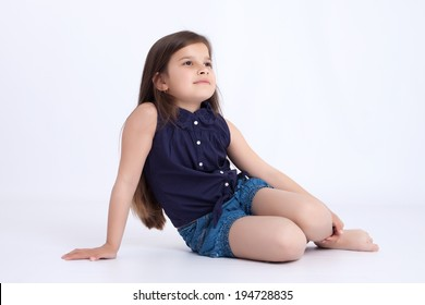Little preschooler girl in denim shorts and a blue shirt sitting on the floor and looks innocent