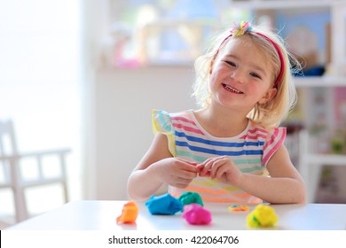 Little preschooler girl playing with plasticine. Happy child, adorable creative toddler playing with colorful modeling compound, sitting at white table in bright sunny room at home or kindergarten