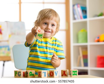Little preschooler kid boy playing with toy cubes and memorizing letters. Early education concept