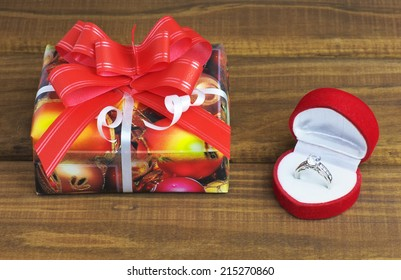 A little present box and box with ring on wooden table