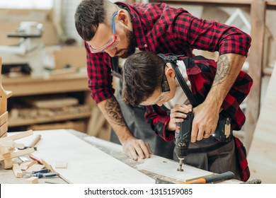 Little pre-teen boy helps his father, working as woodworker, to drill holes in a wooden plank. Close-up of young male carpenter in protective eyewear teaching his son to work with wood in his workshop