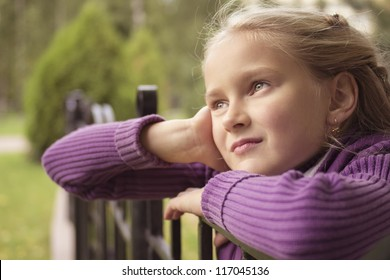 Little preteen girl staring into infinity outdoor in park at autumn