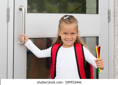A Little Preteen Schoolgirl Holding a Handle of a School Door Showing her Pencils