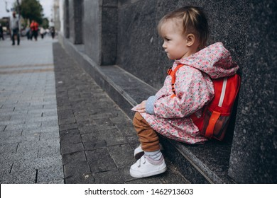 little pretty baby who got lost in the city, a girl in a pink raincoat, with a backpack and a stylish hairstyle sitting next to a large administrative building one by one