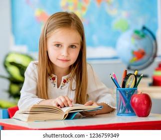Little pretty blond girl sitting in the classroom at the white desk and reading book pointing by finger