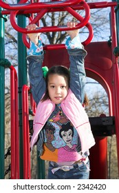 a little pretty child hanging from monkey bars
