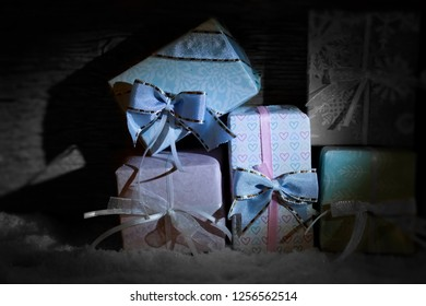 Little pretty christmas presents lie in the snow. A ray of light illuminates the gifts. Beautiful ribbons on noble wrapping paper.