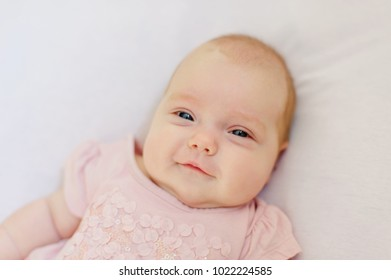Little pretty cute child (infant) 3 month old with deep blue eyes and blonde hair in pink dress with veil
