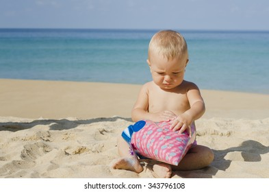 Little pretty cute happy infant european baby girl with big grey eyes and light hair is sitting on the beach near the sea in pink hat