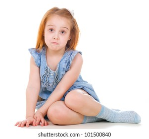 Little pretty ginger girl with funny face sitting on the floor on white background