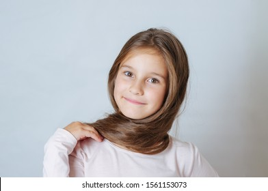Little pretty girl age 6-7 years with very long hair expresses emotional joy and a smile on a white background