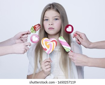 little pretty girl with big candy. Studio ashion photography of kid in white dress. Beautiul model eating sweet lollipop.