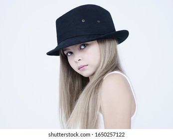 little pretty girl in black classic hat. Studio ashion photography of kid in white dress. Beautiul model on white background.