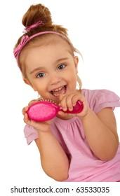 Little pretty girl combing her hair