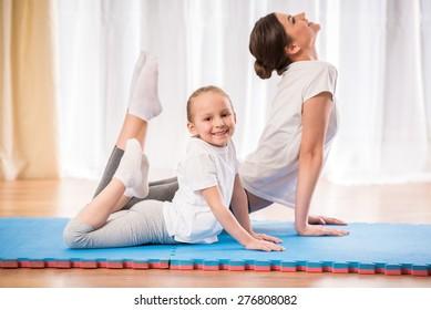 Little pretty girl doing yoga exercises on rug at home.