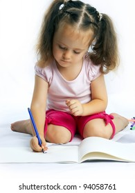 little pretty girl draws with markers on a white background isolated