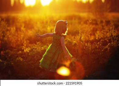 A little pretty girl in a green dress running after the rabbit on a sunny summer evening. Kids are playing