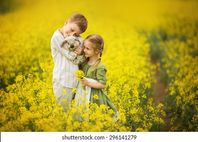 Little pretty girl in green dress with white apron and young boy holding a rabbit in the field of flowering yellow mustard on a sunny summer day. Kids and nature. Children in country. Beautiful flora