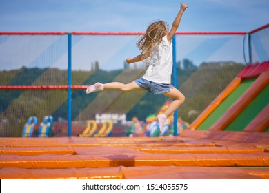 Little pretty girl having fun outdoor. Jumping on trampoline in children zone. Happy girl jumping on the yellow trampoline in Amusement park