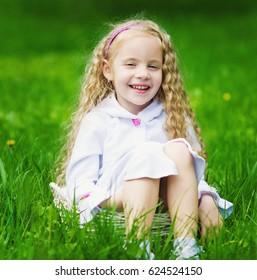 Little pretty girl having fun in the green garden