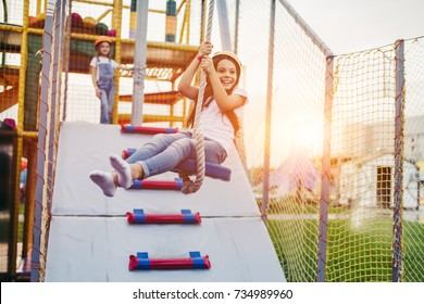 Little pretty girl is having fun outdoor. Playing in children zone in amusement park.