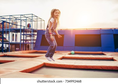 Little pretty girl having fun outdoor. Jumping on trampoline in children zone. 