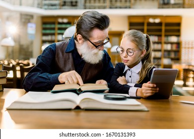 Little pretty girl and her handsome bearded grandfather sitting in vintage library, reading books, using digital tablet. Concept of education for all generations and age