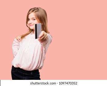 little pretty girl  holding a credit card. paying, money or savings concept. happy expression