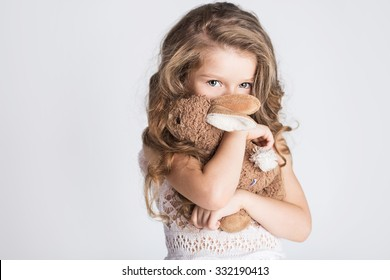 Little pretty girl hugging her toy rabbit and hiding her face with embarrassment or shame or modesty