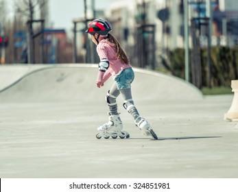 Little pretty girl on roller skates in helmet at a park. back view