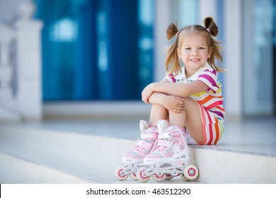 Little pretty girl on roller skates in helmet at a park. Cheerful preschool girl wearing inline roller skates and protective equipment