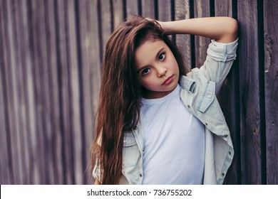 Little pretty girl outdoor. Fashionable child posing on the background of wooden fence.