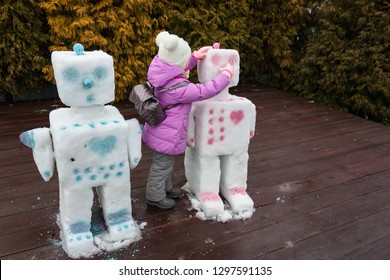 A little pretty girl repairs snowman robots that began to melt because spring came. Concept. Hi, Hello spring!