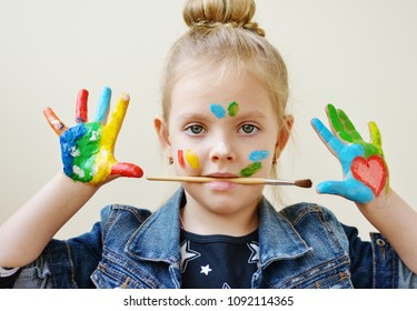 little pretty girl showing painted hands and holding brush in mouth