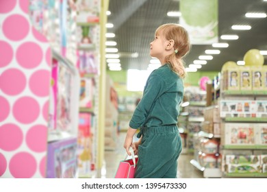 Little, pretty girl standing near shelves with big choice of children toys and choosing. Child holding pink shopping paper bag. Concept of entertainment and development for children.