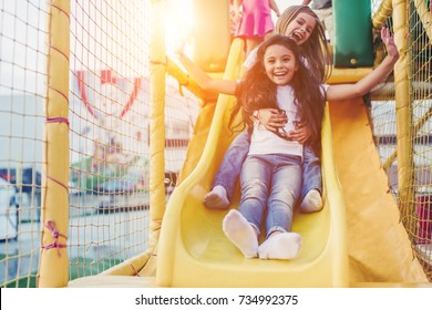 Little pretty girls having fun outdoor. Playing in children zone in amusement park.